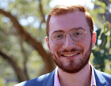 Young man with red hair and beard smiling