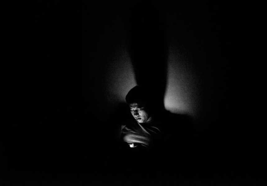 Black-and-white image of man in shadow