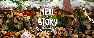 View of colourful table filled with food with Share a Meal Share a Story superimposed