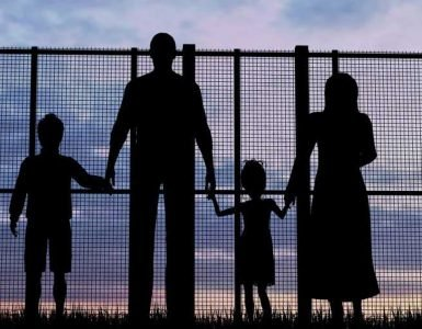 Silhouette of family holding hands behind wire fence