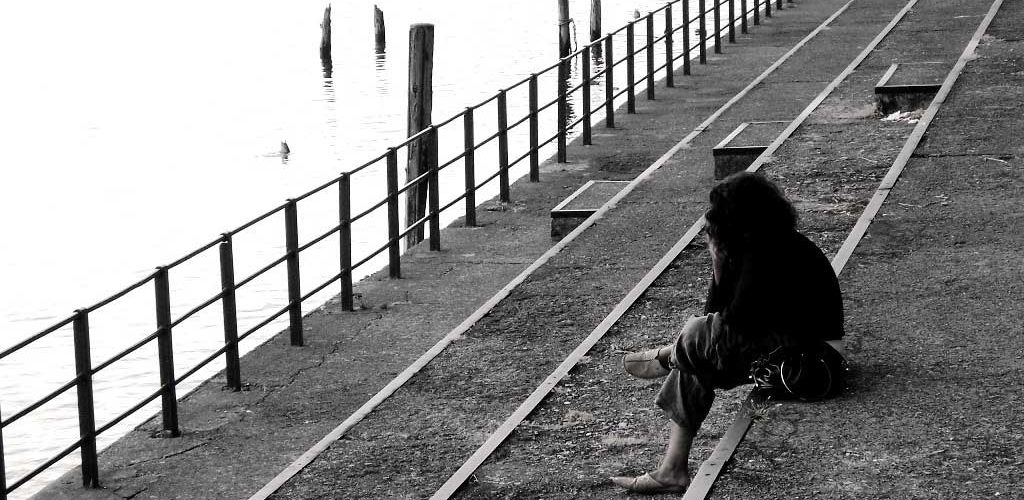 Woman sitting on stairs and looking at lake over railing