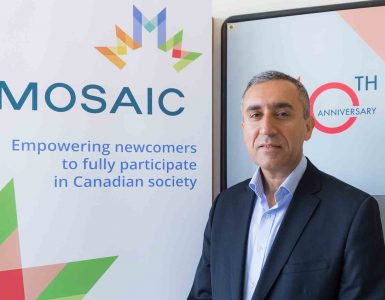 Man in blue suit standing next to poster of MOSAIC Empowering newcomers to fully participate in Canadian society banner