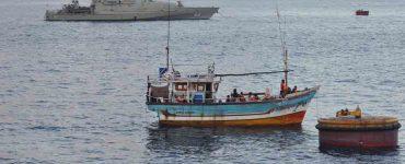 Small fishing boat next to navy boat