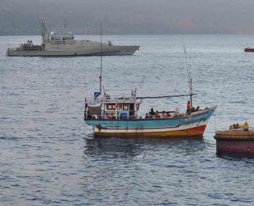 Small fishing boat next to navy boat