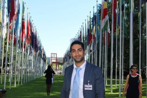 Young man in blue jacket and light blue tie in front of UN avenue of flags