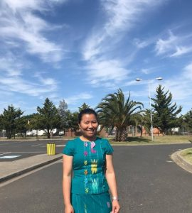Woman in green top standing in front of street with blue sky