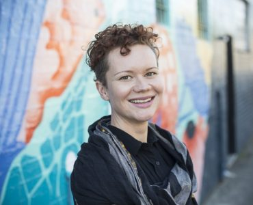 Woman with short curly hair in front of colourful mural