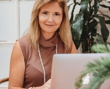 Woman with blonde hair smiling in front of laptop