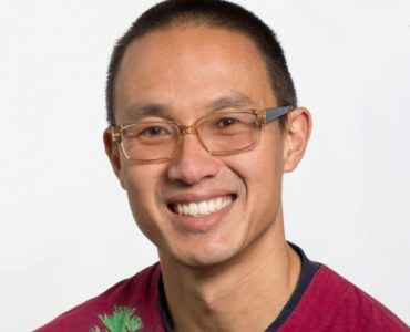 Man with glasses in red shirt with a fern in front