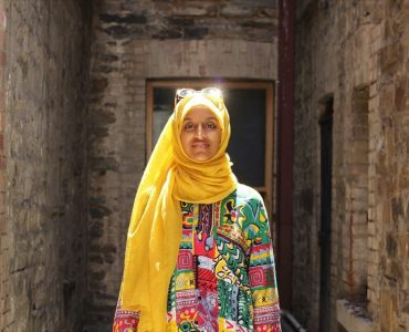 Woman standing in brick cul de sac with glass door in bright yellow headscarf with glasses on head and colourful top