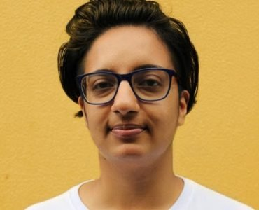 Person with brown hair, black glasses in white shirt and yellow background