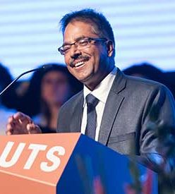 Man in suit and glasses behind UTS lectern