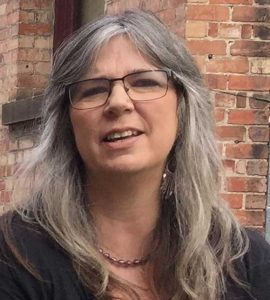 Woman with black-rimmed glasses and long grey hair in front of brick wall