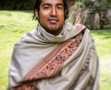 Man wrapped in colourful shawl