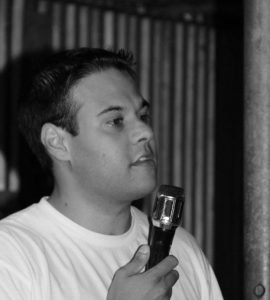 Black and white photo of man holding microphone in white t-shirt