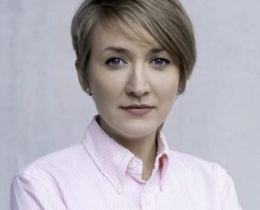 Young woman with short hair in light pink shirt