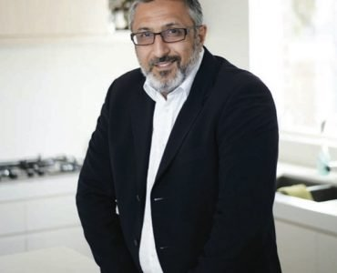 Man in black suit with glasses and white shirt