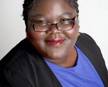 Woman in blak suit and glasses with blue shirt