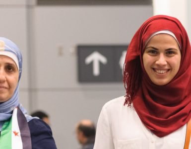 Sponsors, family, and Canadians simply wishing to welcome their new neighbours await the first plane's arrival of Syrian refugees at Toronto's Pearson International Airport.