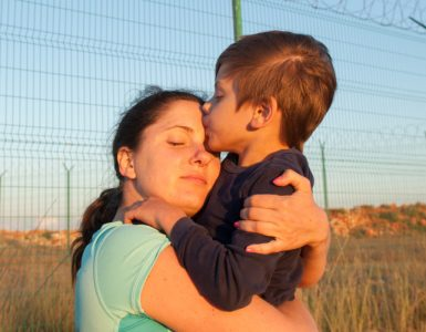 Mother hugging and kissing child on state border with barbed wire