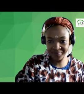 Woman wearing headset in purple patterned top with green background